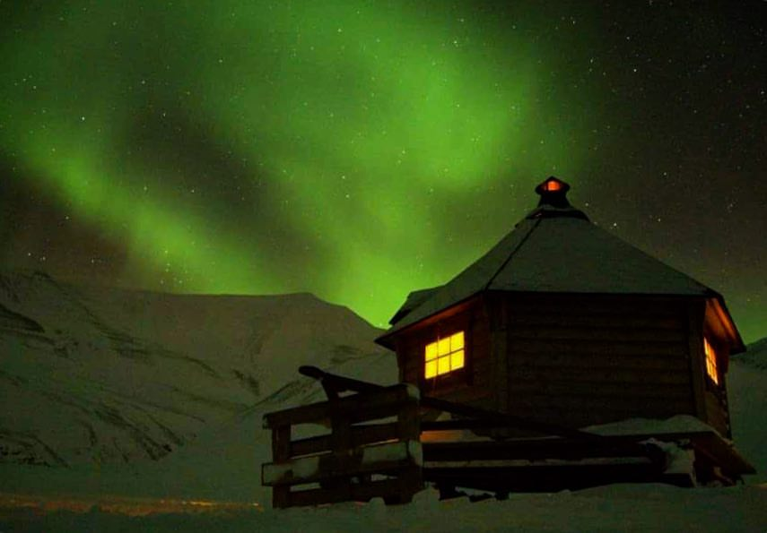 Warm up over dinner in our cabin in during your northern lights trip on Svalbard